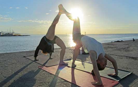 Travelers on their honeymooners enjoy sunrise yoga on the beach in Barcelona.