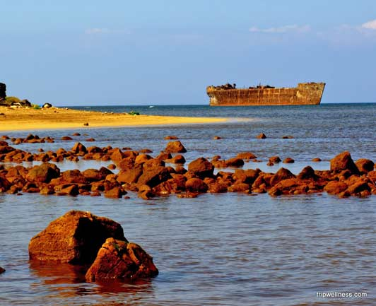 The hull of a rusty Navy ship sticking out of the water can be seen from Shipwreck Beach on Lanai.