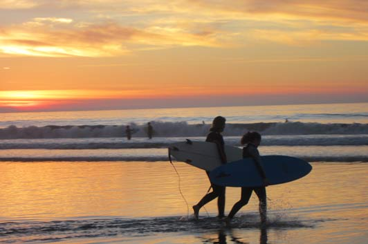 Surfers at sunset, La Jolla Shores Beach, San Diego, California.