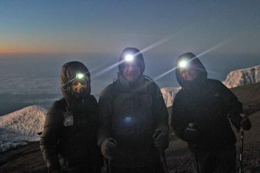 Personal transformation: headlights illuminate the path to the summit during the midnight ascent.
