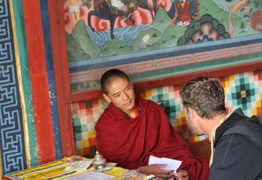 A Northwest Rafting guest talks with a young Buddhist monk.
