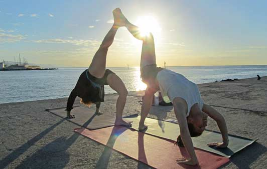 Travelers on their honeymooners enjoy sunrise yoga on the beach in Barcelona.
