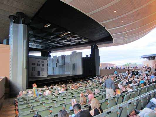 Santa Fe Opera patrons can see the lights of Los Alamos in the distance.