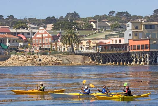Kayaks provide a good view of marine life on Monterey Bay and Cannery Row buildings.
