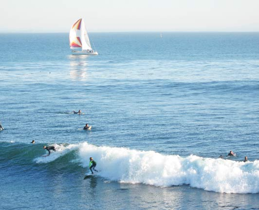 Classic California roadtrip view: surfers and sailboats.