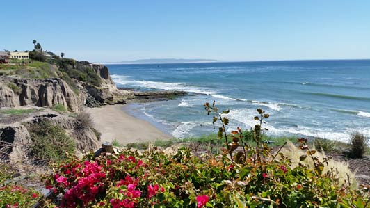 In Shell Beach, native grasses and red bougainvillea bloom on the oceanfront bluffs.