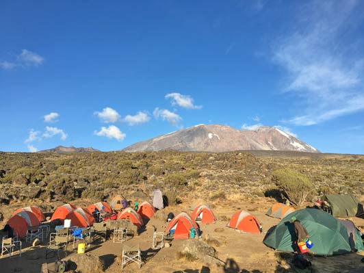 Dawn breaks on a gorgeous day at base camp, and Mount Kilimanjaro beckons in the distance.
