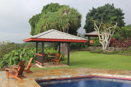 """A gazebo and massage """"hale"""" are in the garden near the pool."""