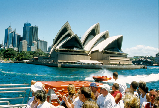 Sydney Opera House, with its famous sail-like roof, as seen from the harbor.