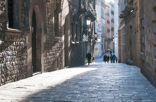 A narrow street slices through apartment buildings in the Gothic Quarter - a favorite spot on Barcelona walking tours.