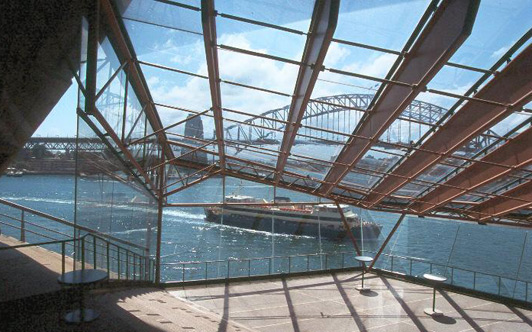 """Sydney Harbour and the """"coat hangar"""" bridge from inside the Sydney Opera House."""